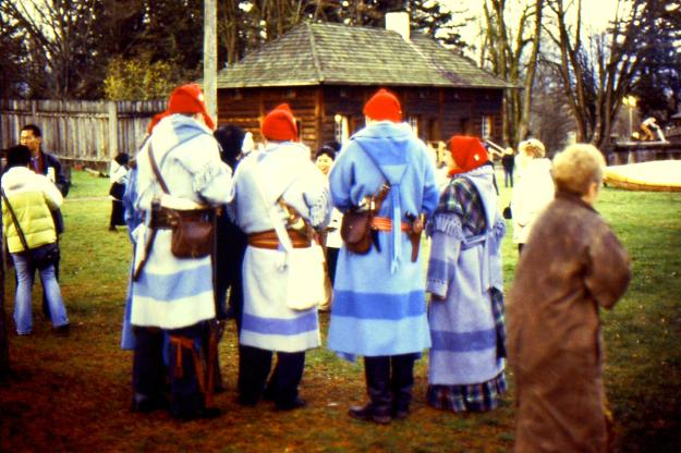 re-enactors visiting Fort Langley National Historic site dressed in blanket coats from the back